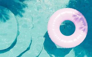 blauwe bodem zwembad met ronde trap van bovenaf gezien met een roze vlotter en schaduw van palmbomen, 3d render foto