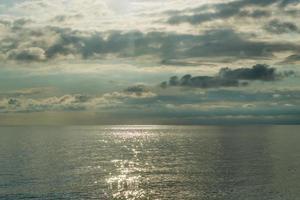 zeegezicht met bewolkte blauwe hemel bij zonsondergang foto