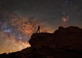 silhouet van een persoon met de Melkweg erachter foto