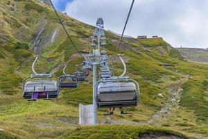 mensen rijden een luchttram of kabelbaan over een berg met bewolkte blauwe hemel in Sochi, Rusland foto