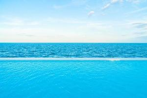 oneindig zwembad met uitzicht op zee en de oceaan op de blauwe lucht foto
