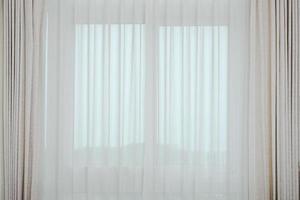 zachte bruine gordijnen in het ochtendlicht vanuit het raam foto