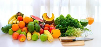 geassorteerde verse rijpe groenten en fruit op tafel met witte gordijn achtergrond foto