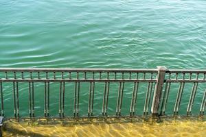 overstroomde dijk naast een metalen hek aan de Angara-rivier in Irkutsk foto