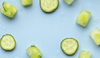komkommers en ijs op blauwe achtergrond foto