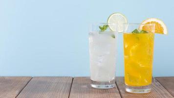 glazen oranje limonade drankje op houten tafel en blauwe achtergrond foto