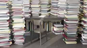 bureau omringd door vele opgestapelde boeken foto