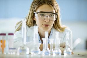 vrouwelijke medisch of wetenschappelijk onderzoeker kijken naar een kolven met oplossingen in een laboratorium foto