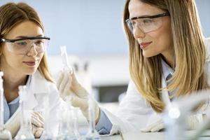 twee vrouwelijke wetenschappelijke onderzoekers kijken naar een kolven met oplossingen in een laboratorium foto
