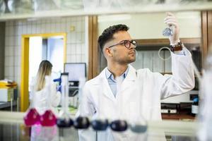 jonge onderzoeker die reageerbuizen controleert foto
