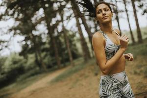 jonge fitness vrouw draait op bospad foto