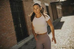 jonge vrouw loopt op straat foto