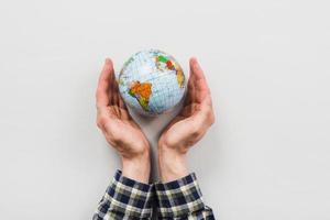 earth globe omgeven door handen op witte achtergrond foto