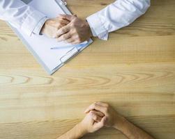 handen van anonieme arts met patiënt aan tafel foto
