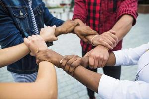 anonieme multiraciale mensen die handen stapelen foto