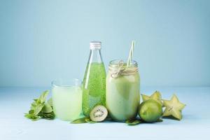 vooraanzicht van groene smoothiedrank op blauwe achtergrond foto