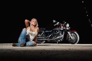 sexy blonde zit in de buurt van haar motorfiets foto