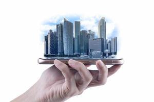 een mensenhand die moderne gebouwen van zakelijk financieel district en handel op smartphone, concept van industriële bouw en succes met technologie houdt foto