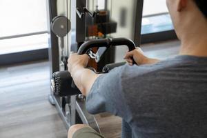 jonge man beginner trainen met halters buigen spieren in een sportschool, sport trainingsconcept foto
