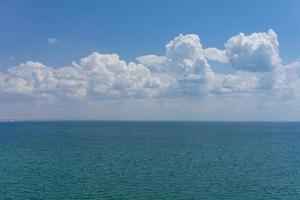zeegezicht van waterlichaam en lucht met gezwollen witte wolken foto