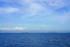bewolkte blauwe hemel boven een watermassa foto