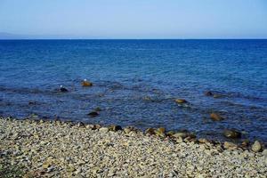 bewolkte blauwe hemel boven een watermassa en een rotsachtige kustlijn foto