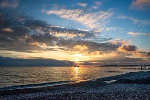 kleurrijke zonsondergang over een watermassa en een rotsachtige kust foto