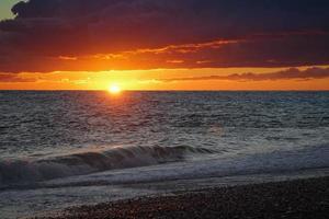 kleurrijke oranje bewolkte zonsondergang over een watermassa foto