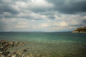 Zeegezicht van een rotsachtige kustlijn bij een watermassa met bergen en bewolkte blauwe hemel in Nakhodka, Rusland foto