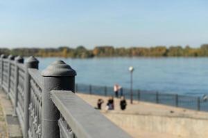 Stedelijk landschap van een metalen hek naast een watermassa met wazige mensen op de achtergrond en een heldere blauwe lucht in Irkutsk, Rusland foto