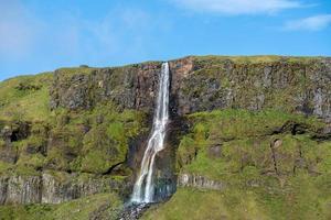 waterval stroomt langs een groene berghelling foto