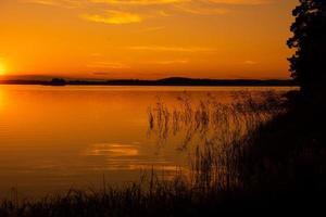prachtig uitzicht over een meer met gloeiend oranje zonlicht foto
