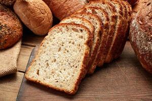 hoop hele en gesneden vers gebakken brood op houten achtergrond foto