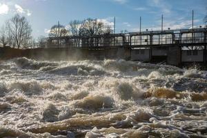 water dat uit een dam van een energiecentrale stroomt foto