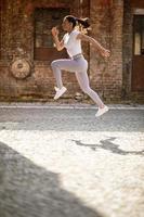 mooie jonge vrouw hoog springen tijdens de training in de stedelijke omgeving foto