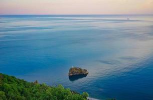 zeegezicht van een rotsachtige kustlijn door een watermassa met een kleurrijke bewolkte hemel foto