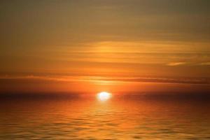 kleurrijke bewolkt oranje zonsondergang met uitzicht op een watermassa foto
