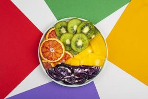 kleurrijk voedselconcept, paarse kool, sinaasappel, kiwi en gele peper foto