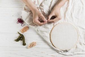 hand met een tamboerframe van naalddraad foto