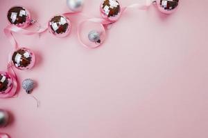 heldere kerstballen op roze achtergrond foto