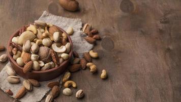 kom met noten en kopieer de ruimte op houten achtergrond foto