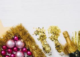 champagnefles met glanzende kerstballen op tafel foto