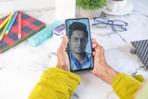 man doet video-overleg met arts aan de telefoon foto