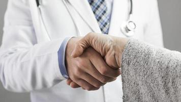 close-up van mannelijke arts en patiënt handen schudden foto