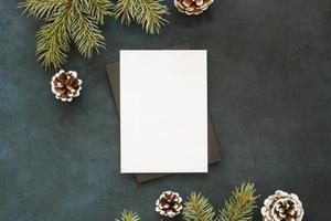 blanco papier omgeven door dennenbladeren en kegels foto