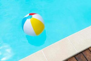 kleurrijke strandbal die op een zwembad drijft foto