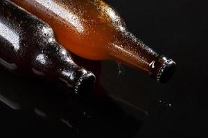 koud bier op zwarte achtergrond foto