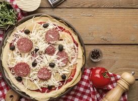 pizza met ingrediënten klaar om te bakken foto