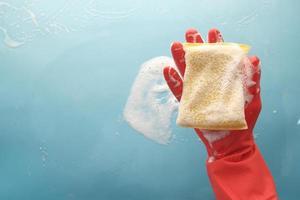 zeepachtige spons in gehandschoende hand foto