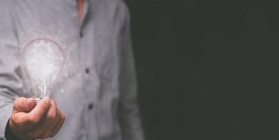 hand van een man met een gloeilamp en versnelling pictogram foto